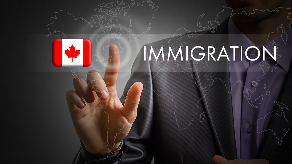 Businessman pressing virtual button with Canadian flag | Canadian Permanent Residency