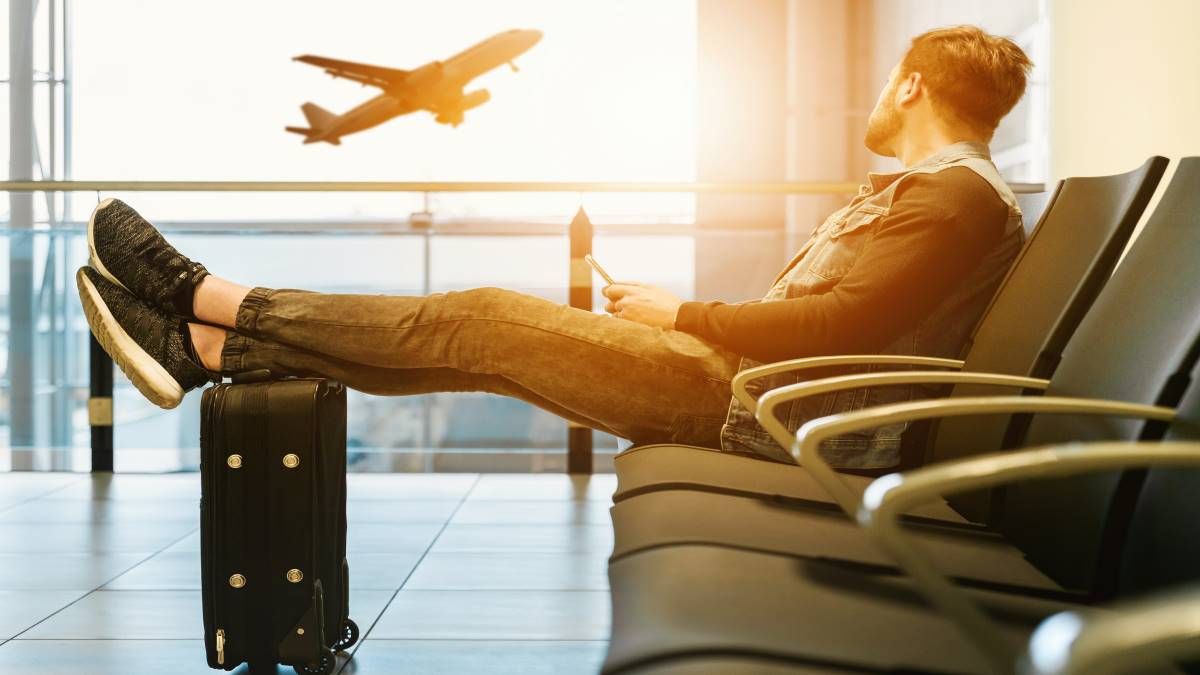 man-sitting-in-airport-waiting-to-board-flight-places-to-visit-in-canada