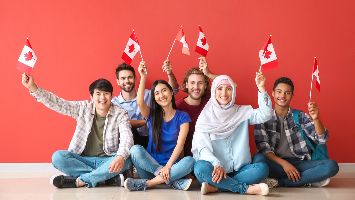 People wavings small Canadian flags | Immigrate to Canada from India in 2021