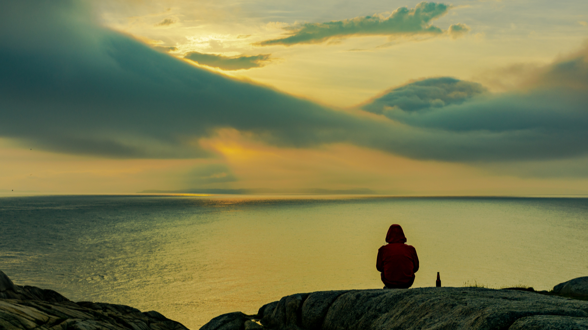 Person sitting down and overlooking lake in Canada