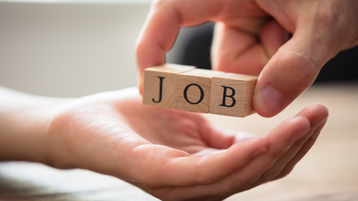 business person's hand holding wooden blocks spelling word job | Post pandemic jobs in Canada