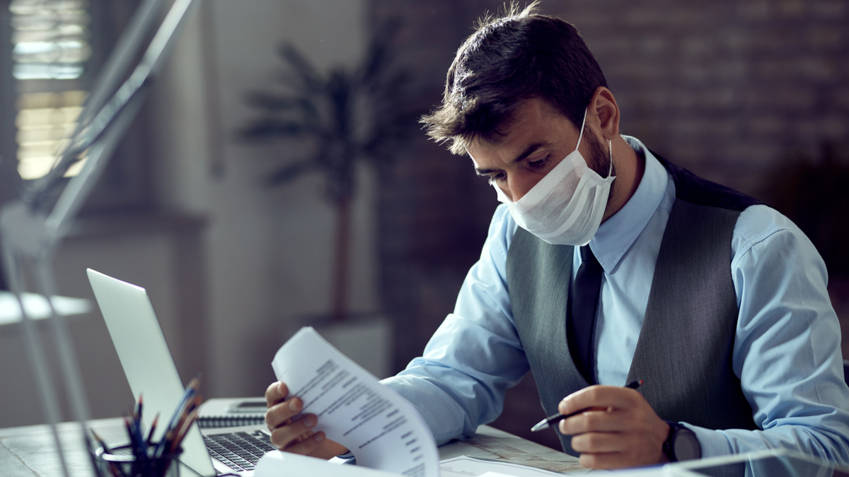 man working through reports wearing mask | Post pandemic jobs in Canada