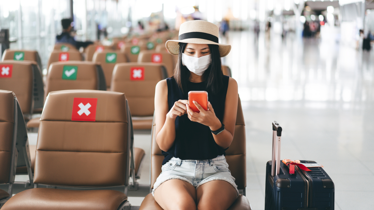 woman sitting at airport with suitcase wearing mask  | Post pandemic jobs in Canada