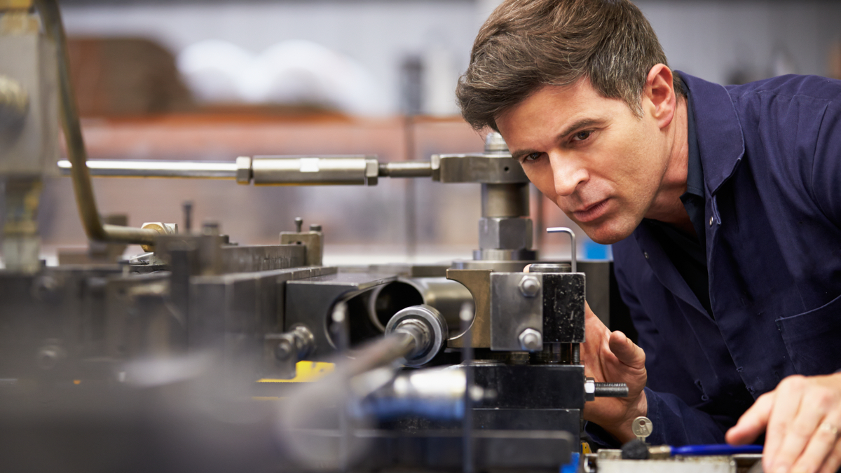 man working on machine in manufacturing  | jobs in Canada