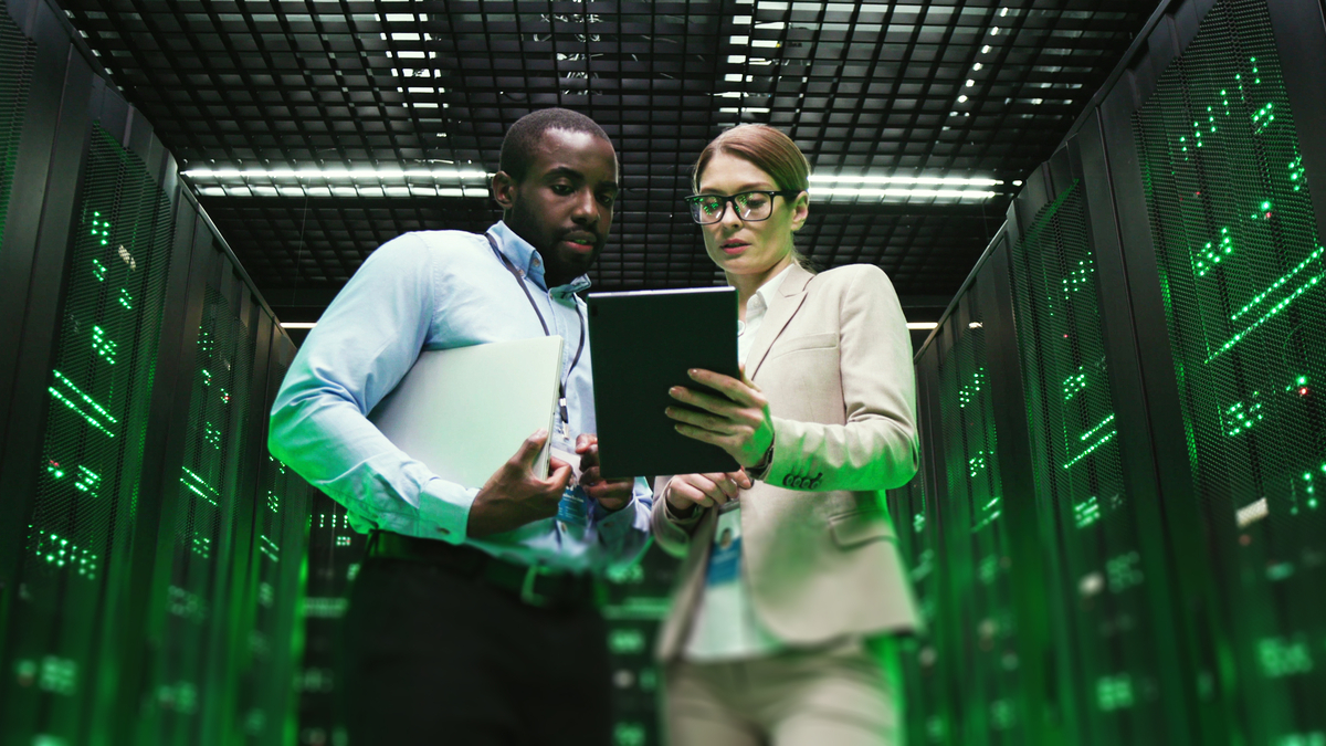 mixed races developers standing at servers storage holding tablet in data center | jobs in Canada