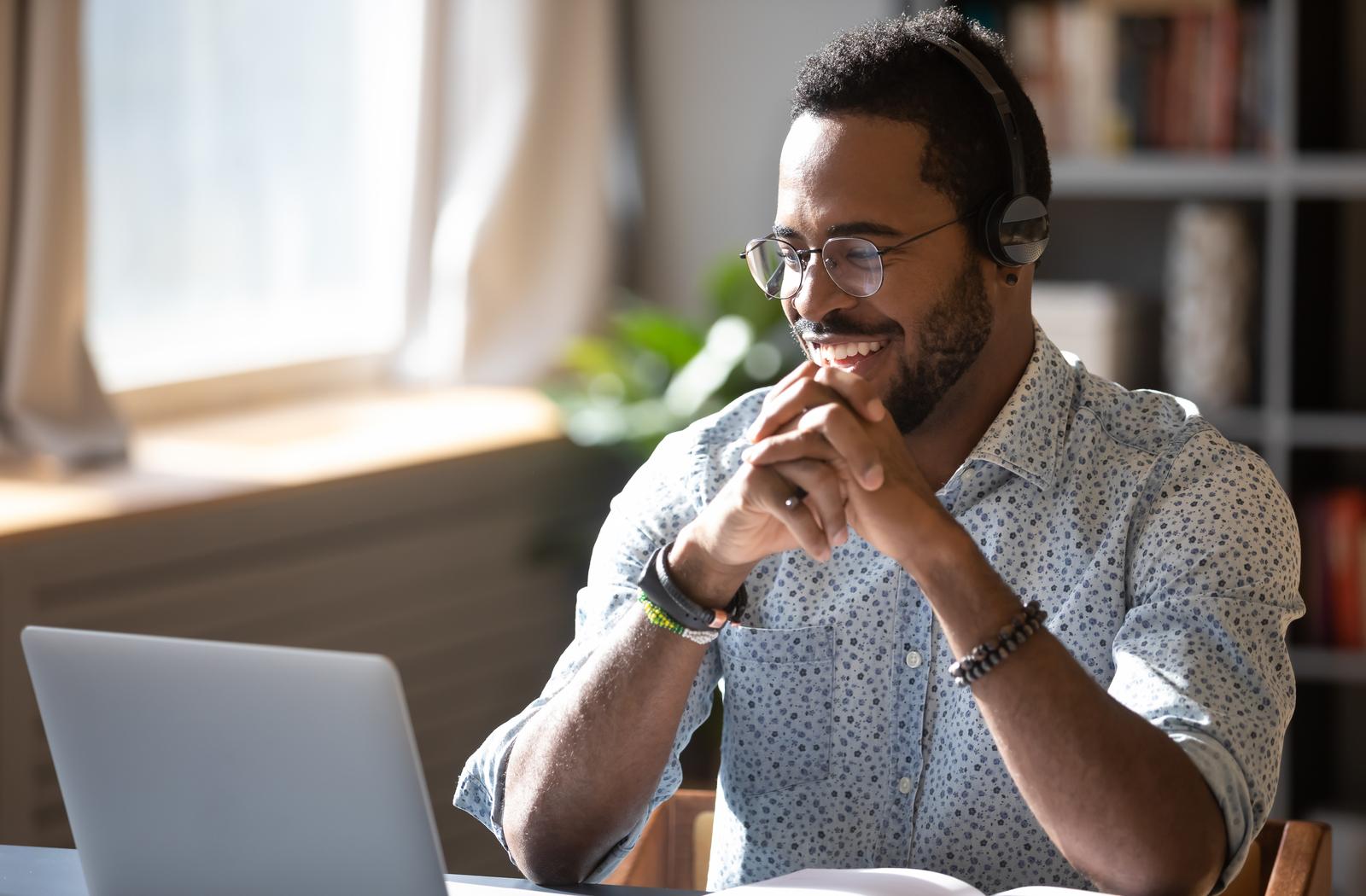 Man smiling at a laptop